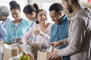 Cheerful young woman laughs along with her husband or boyfriend while volunteering in a community food bank. They are sorting through food donations. Volunteers are working in the background.